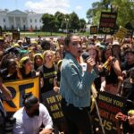 AOC Joins Climate Protesters With 'Biden You Coward, Fight For Us' Signs Outside White House 5